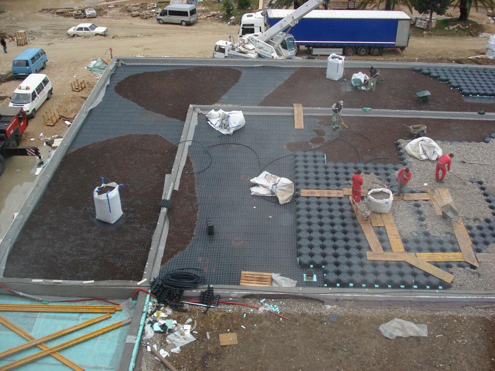 Slaganje slojeva zemlje i nivelatora na zelenom krovu iznad welnesa.